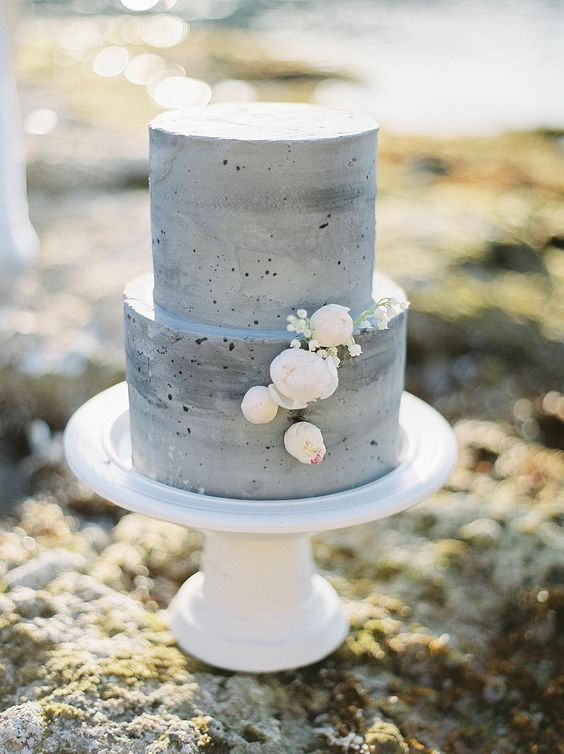 a grey concrete wedding cake with tender blush and white blooms is a stylish idea for a modern wedding