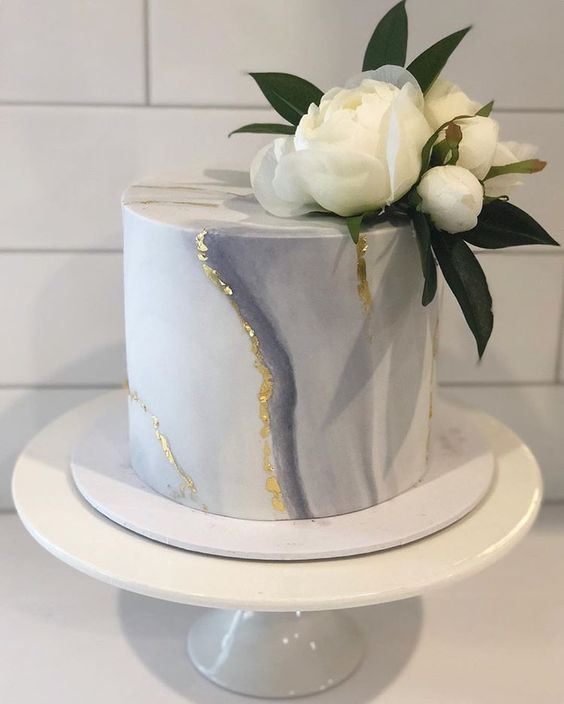 a grey marble mini cake with gold leaf and fresh white blooms and leaves is an elegant and chic idea