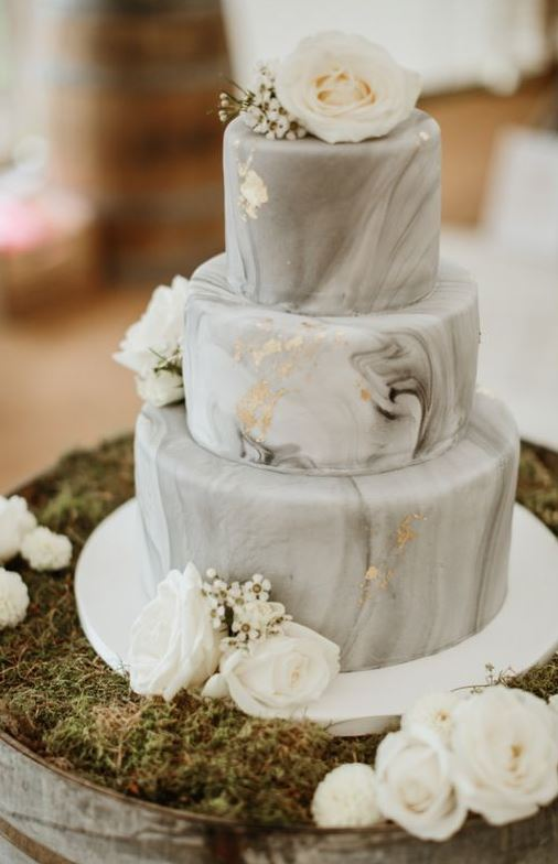 a grey marble wedding cake with gold leaf and white blooms is pure and timeless elegance