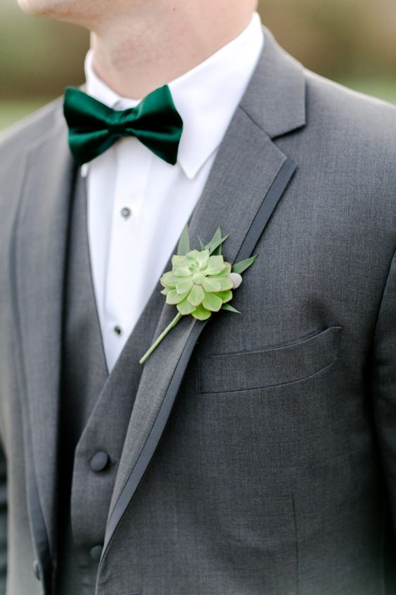 a grey three piece tux with a white shirt, an emerald bow tie and a succulent boutonniere compose a modern refined look