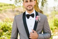 a grey tuxedo with black lapels, a black bow tie with polka dots and a white shirt with black buttons