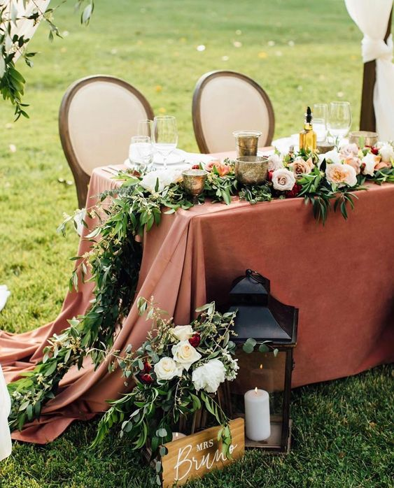 a large candle lantern, florals, a sign, a greenery and bloom table runner and candleholders for elegant decor