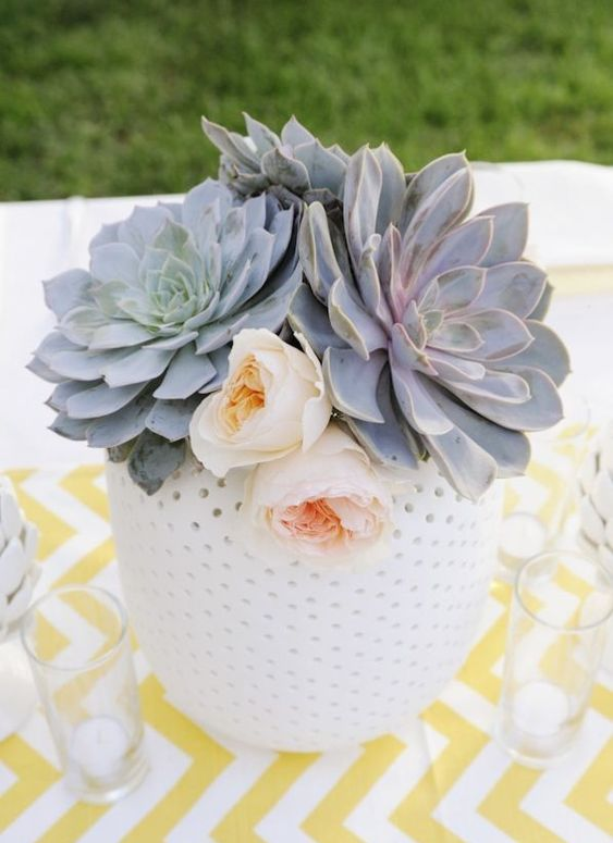 a large polka dot vase with large succulents and blush blooms is a cool and fresh wedding centerpiece idea