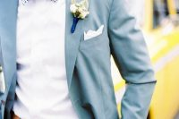 a light blue suit, a bold printed blue bow tie, a light brown belt for a cheerful summer look