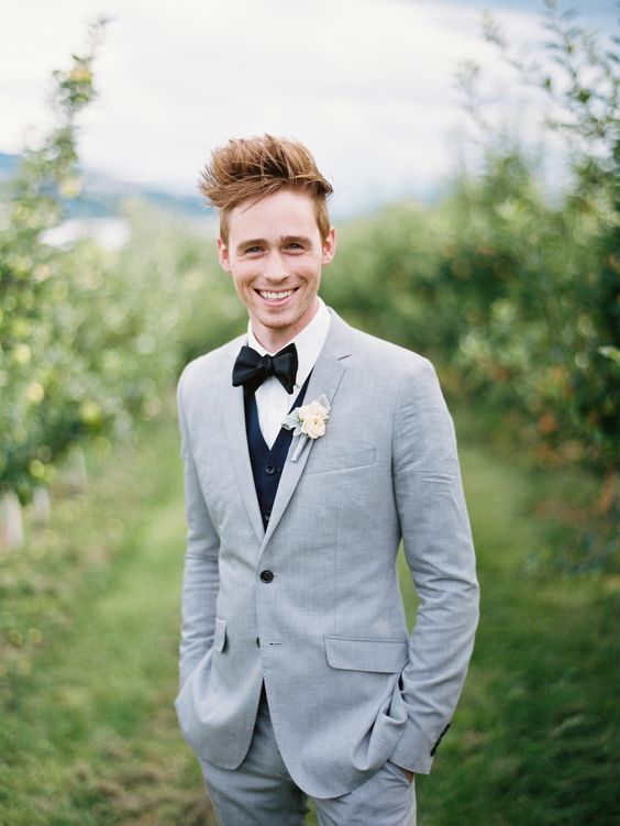 a light grey suit, a black vest, a black bow tie for a fresh take on classics