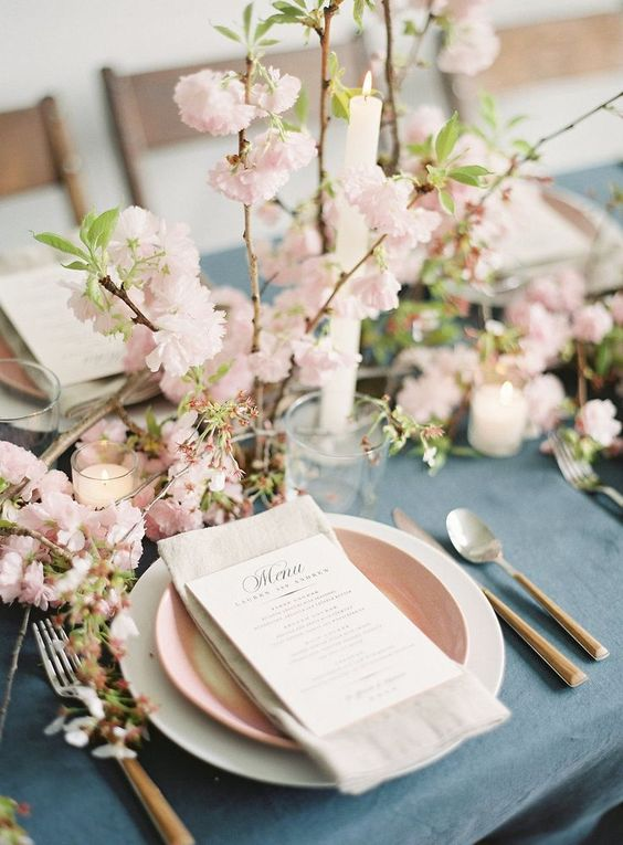 a lovely spring wedding tablescape with a blue tablecloth, pink and white plates, blooming branches, greenery and candles
