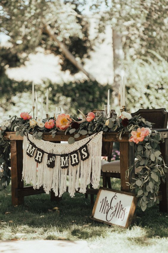 a lush greenery and bloom table runner, a banner and some macrame plus a sign to mark the table