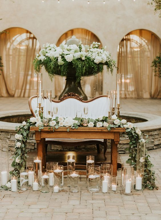 a lush greenery and bloom table runner, lots of usual and floating candles and a lush floral installation