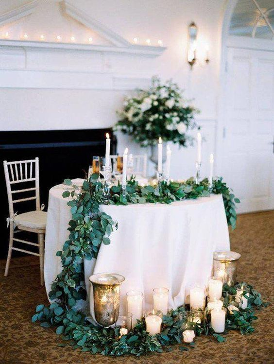 a lush greenery table runner, lots of candles and urns with candles for an elegant touch and to mark the table