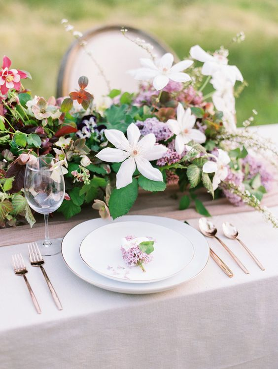 a lush spring wedding tablescape with a catchy and dimensional floral centerpiece, elegant plates and cutlery