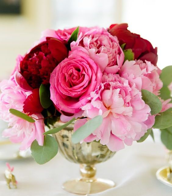 a lush wedding centerpiece of a gold bowl and pink and deep red blooms plus foliage is a bright idea