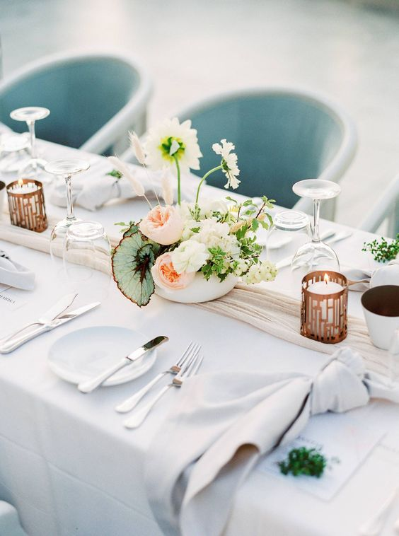 a modern and refined spring wedding table with neutral linens, candles, a catchy floral centerpieces and simple cutlery