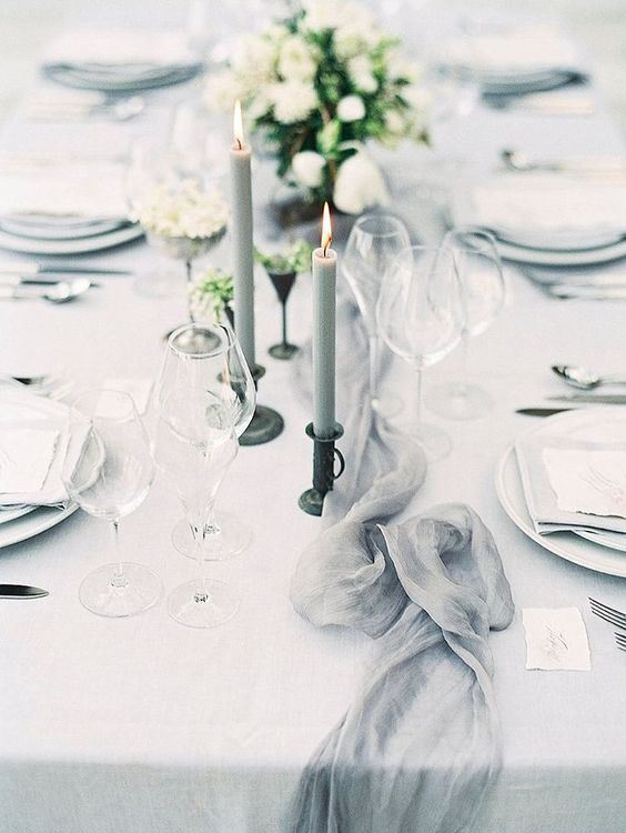 a modern romantic wedding table setting with an airy grey runner, candles, plates and neutral blooms is super chic