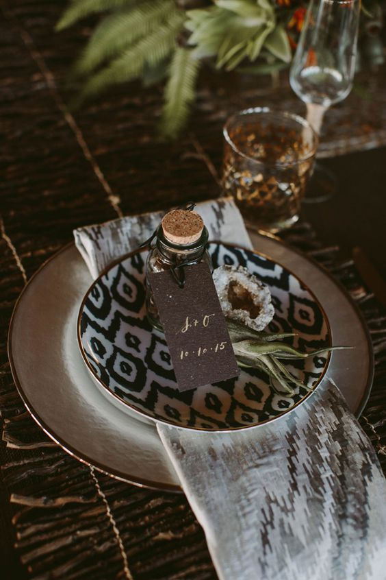 a modern safari themed wedding with a white and a printed plate, geodes, an air plant and a favor in a bottle