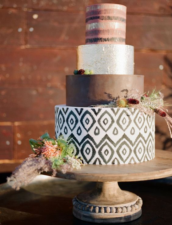 a modern safari wedding cake with a brown, silver, striped and ikat tiers, with dried blooms and greenery