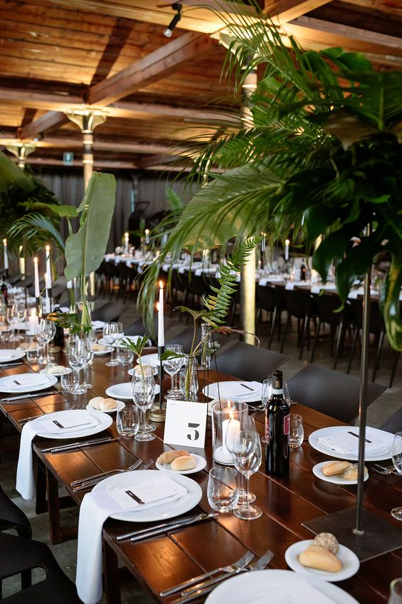 a modern safari wedding tablescape with white linens, porcelain and candles, tropical leaves and elegant glasses