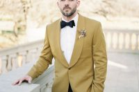 a mustard tux, a white shirt, black bow tie and a dried bloom boutonniere for a bright summer or fall outfit