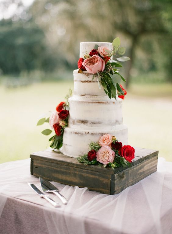 a naked wedding cake decorated with pink and red blooms and greenery is a chic and cool idea to rock in winter