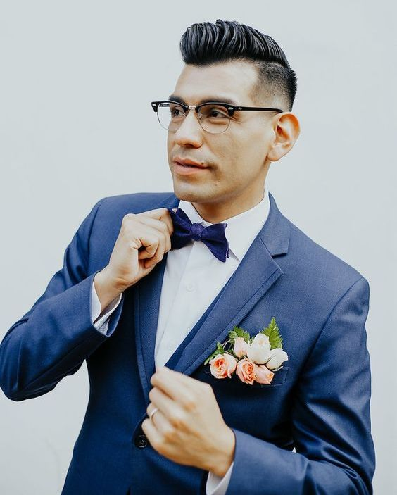 a navy suit, a navy bow tie and a coral and blush floral boutonniere for a whimsy and bright groom's look