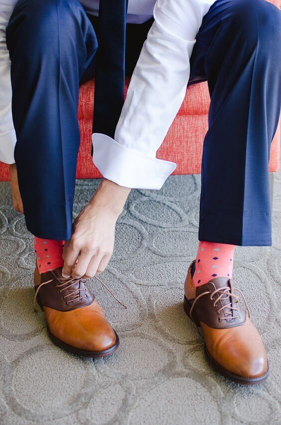 a navy suit spruced up with printed coral socks and with whimsy brown shoes