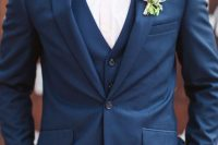 a navy three-piece suit, a blush shirt, a purple bow tie and a floral boutonniere for a bold summer or fall look