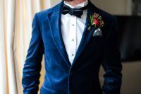 a navy velvet blazer, a white shirt with black buttons, a black bow tie and a bright floral boutonniere for fall or winter