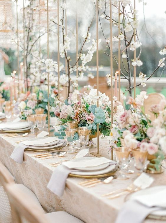 a neutral spring wedding tablescape with blooming branches, floral centerpieces, neutral linens, gold cutlery and gold rimmed glasses