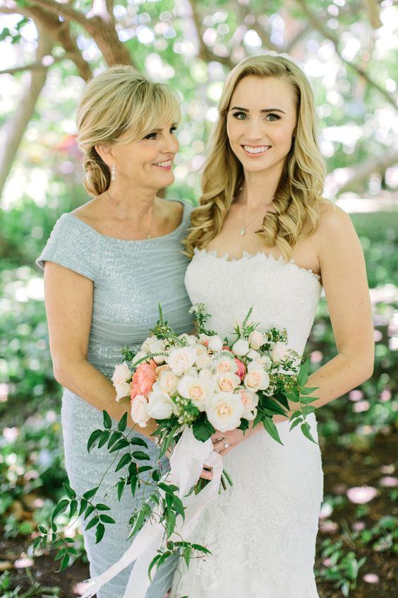 a pastel blue fitting and shiny midi dress with a bateau neckline and cap sleeves plus shiny earrings is a wow idea for a spring or summer wedding