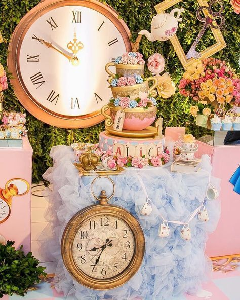 a pastel wedding cake table in pink and blue, with bright blooms and oversized clocks looks very whimsy
