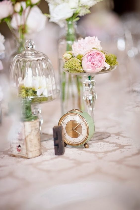 a pastel wedding centerpiece with pink blooms, moss and a small green clock for a vintage wedding