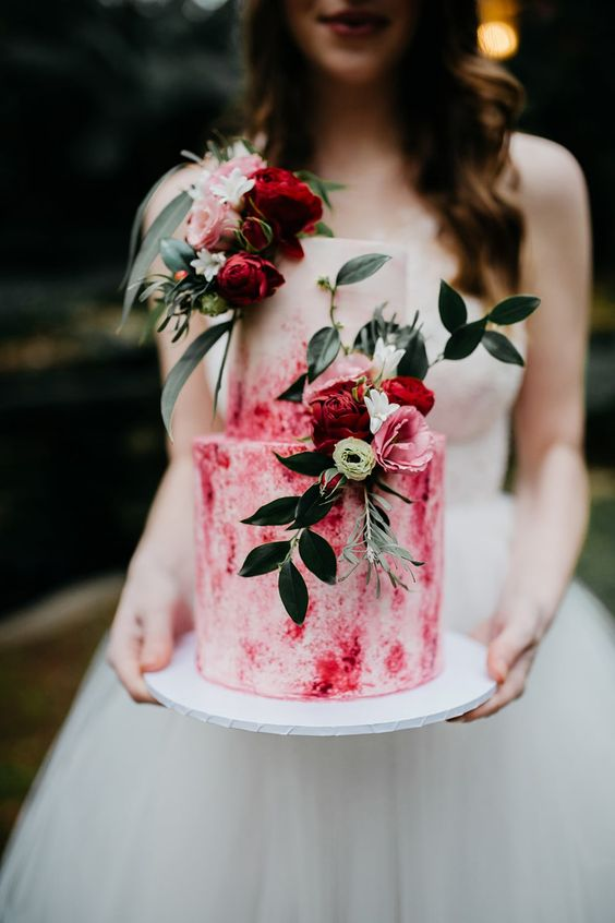 a pink watercolor wedding cake decorated with pink and red blooms and foliage is a bold modern idea