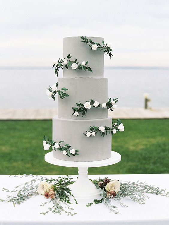 a plain grey wedding cake with white blooms and greenery is a chic and modern idea with a touch of romance