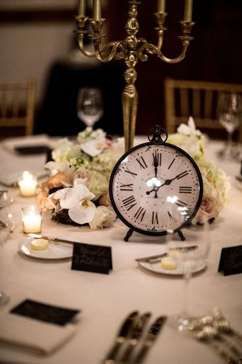 a refined and chic wedding centerpiece with white and pastel blooms, a large candelabra and a large clock
