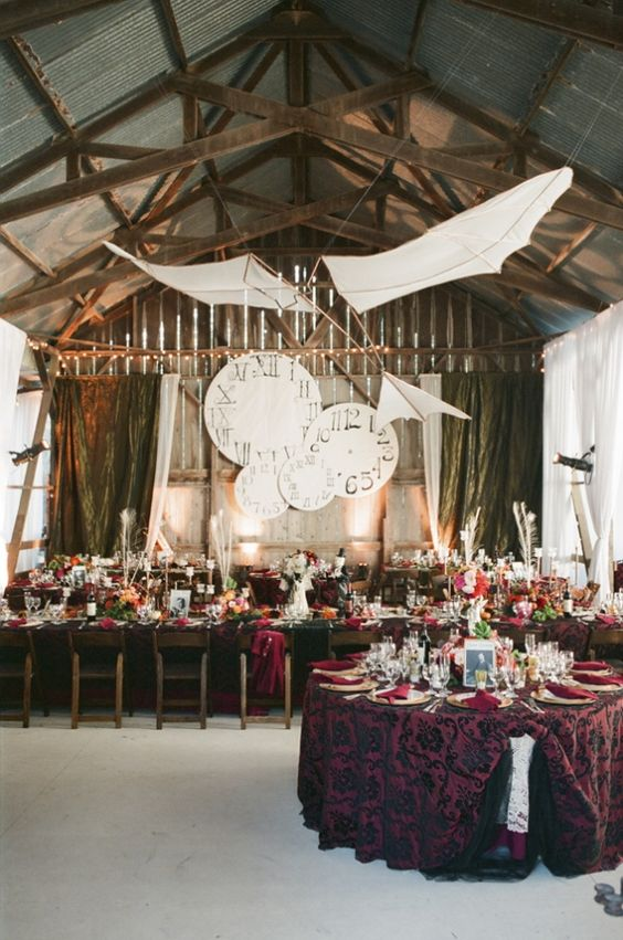 a refined and chic wedding venue decorated with paper planes and cardboard clocks