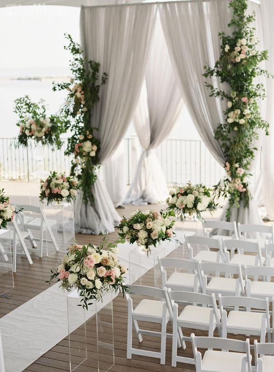 a refined ceremony space with grey curtains, pastel and neutral blooms and greenery is a chic option to go for