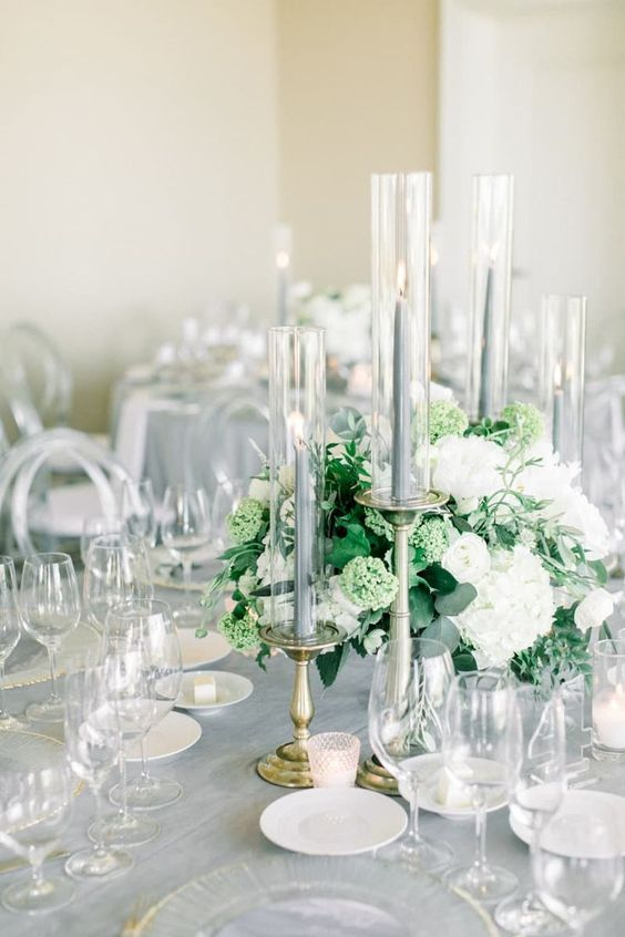 a refined grey wedding tablescape with neutral blooms and greenery and tall grey candles and a tablecloth