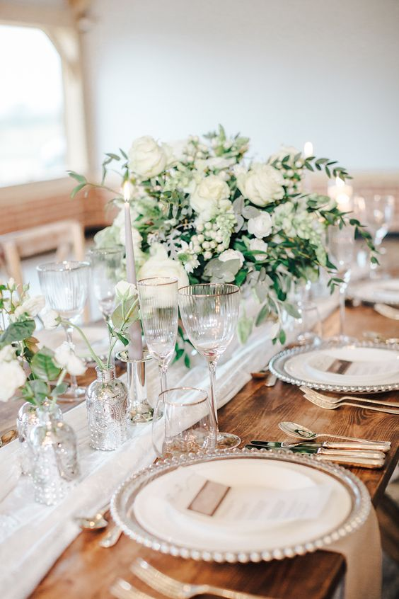 a refined neutral spring wedding table with neutral linens, blooms and greenery, candles and mercury glass vases