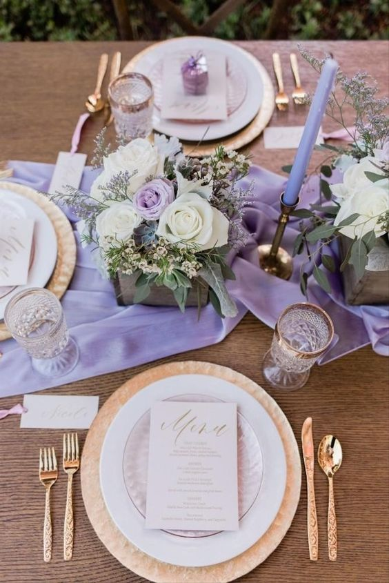 a refined spring wedding tablescape with a purple runner and candles, neutral and purple blooms and greenery, gold cutlery and gold rimmed glasses