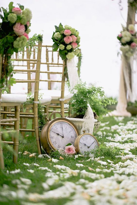 a refined wedding aisle decorated with white petals, pink blooms, greenery and large clocks looks chic
