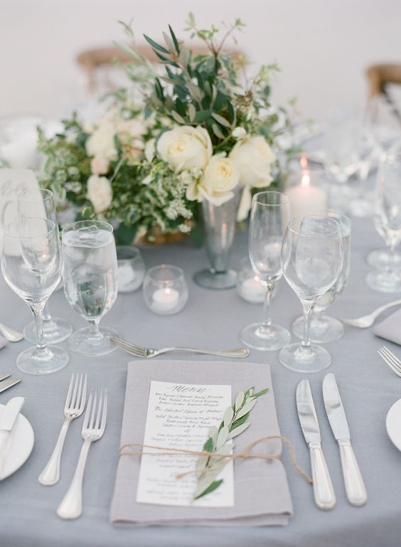 a romantic grey wedding table setting with a grey tablecloth, napkins, neutral blooms and lots of candles