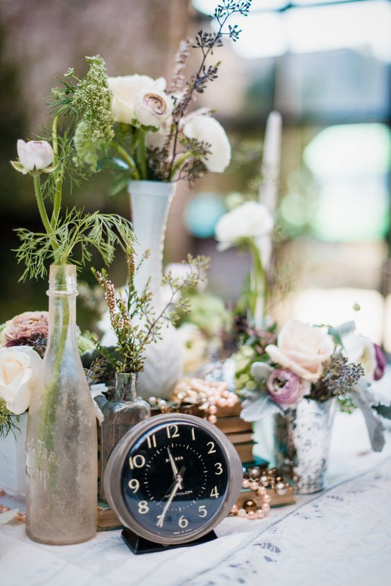 a romantic vintage wedding centerpiece with pink and pastel blooms, greenery, pearls and a black clock