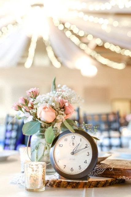 a rustic wedding centerpiece of pink and white blooms and greenery, candles and a large clock on a wood slice