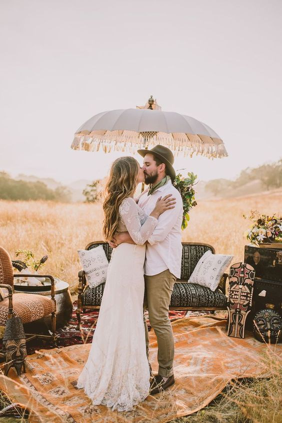 a safari-themed wedding lounge with layered rugs, vintage boho furniture, greenery and blooms and an umbrella