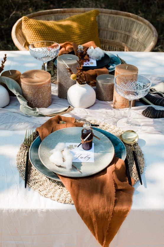 a safari-themed wedding tablescape with woven chargers, rust napkins, grey plates, muted tone candles and blooms in a vase