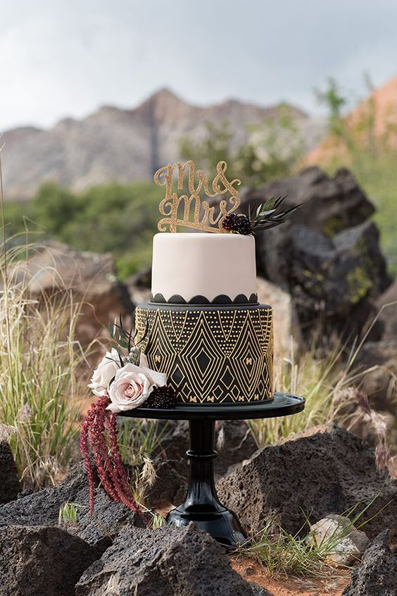 a safari wedding cake with a plain white and black and yellow patterned tier, neutral and dark blooms and a gold topper