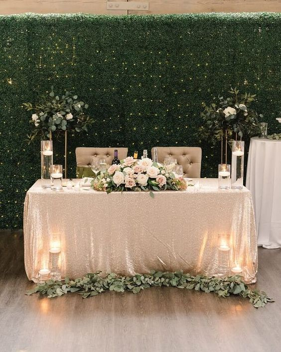 a sequin tablecloth, a greenery runner, candles, a floral centerpiece with some foliage for a touch of glam