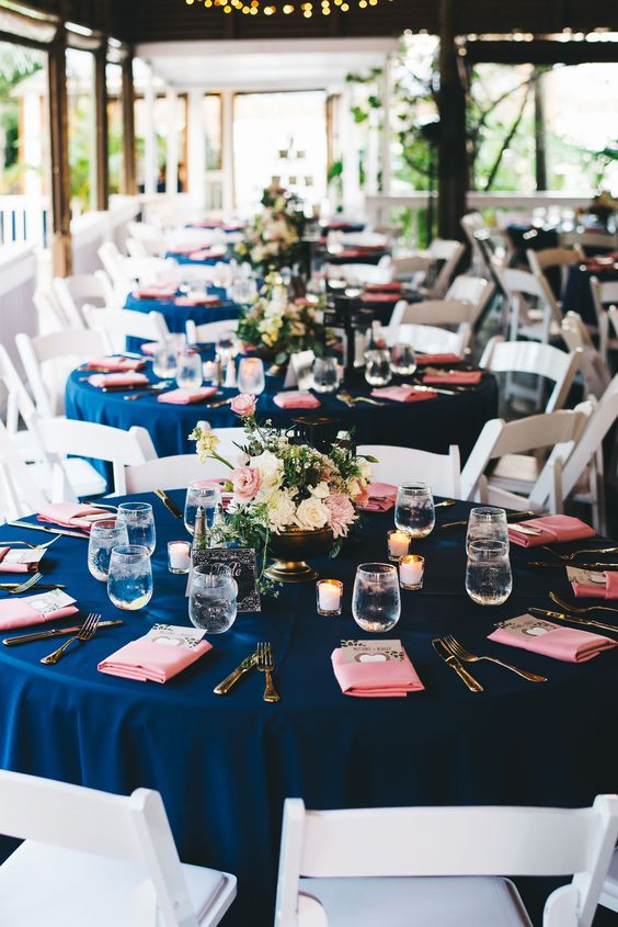 a simple and elegant wedding tablescape with a navy tablecloth, coral napkins, candles and ivory and coral blooms