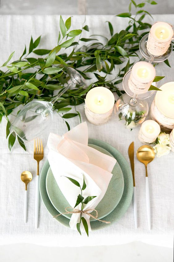 a simple and fresh spring wedding table with greenery, brich bark wrapped candles, green plates and gold and white cutlery