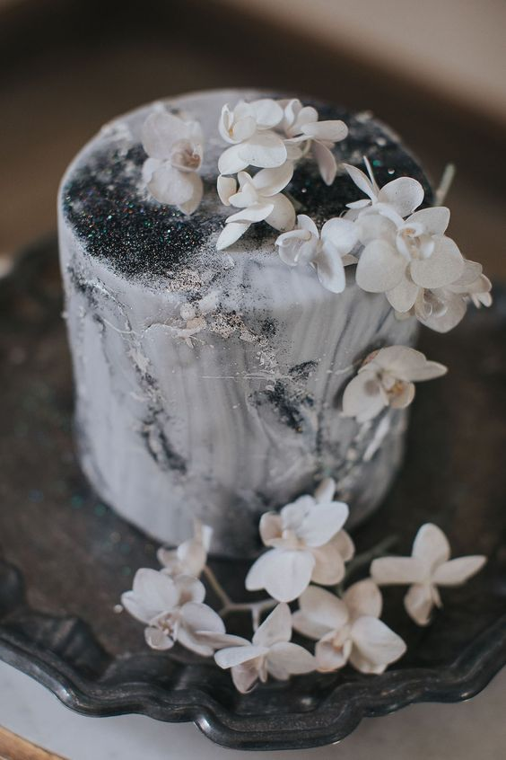 a sophisticated celestial grey marble wedding cake topped with white orchids and with silver leaf is wow