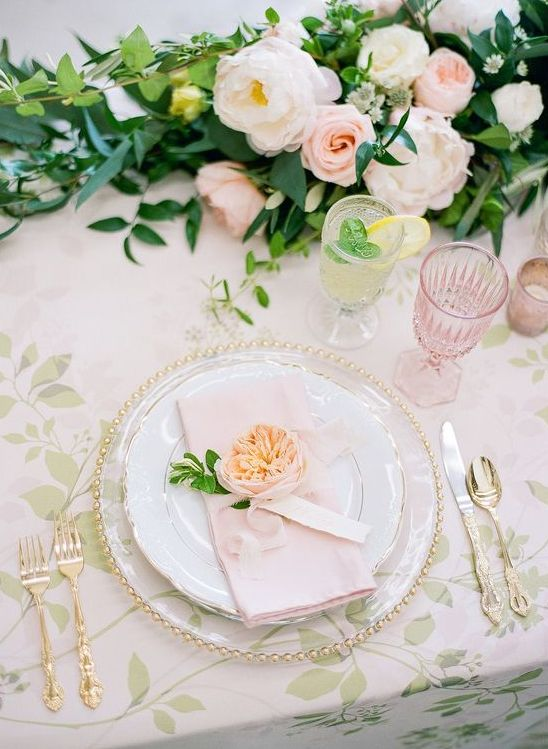 a sophisticated spring wedding table with gold cutlery and sheer plates, a botanical tablecloth, blush and neutral blooms and greenery